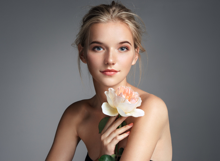 Photo pour Charming young girl with perfect makeup. Photo of blonde girl with rose on grey background. Skin care concept - image libre de droit