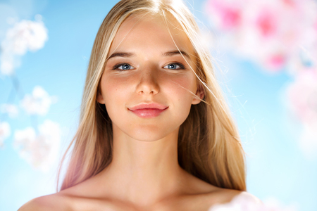 Photo pour Beautiful blonde girl around spring flowers. Youth and skin care. Spring. - image libre de droit