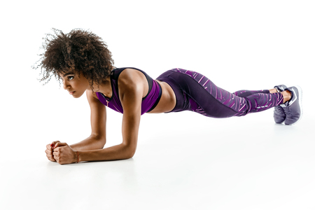Photo pour Beautiful young girl doing plank exercise. Photo of african girl in silhouette on white background. Fitness and healthy lifestyle concept - image libre de droit