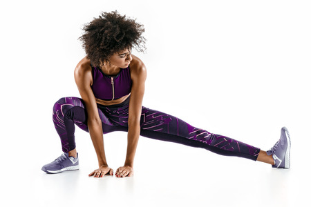 Photo pour Beautiful young girl stretching her hamstrings. Photo of sporty girl doing exercising on white background. Sports - image libre de droit