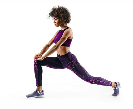 Foto de Fitness african girl doing stretching workout. Full length shot of young girl on white background. Stretching and motivation - Imagen libre de derechos