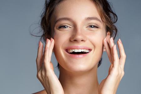 Foto de Image with beautiful brunette girl touching her face on grey background. Close up. Beauty & Skin care concept - Imagen libre de derechos