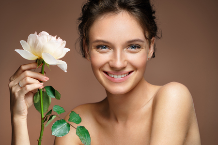 Foto de Beautiful smiling girl. Photo of young girl with rose on beige background. Beauty & Skin care concept - Imagen libre de derechos