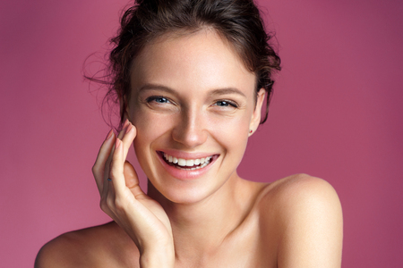 Photo pour Happy young girl touching her perfect skin on pink background. Beauty & Skin care concept - image libre de droit