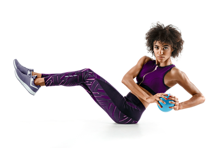 Photo pour Beautiful young girl working out with fitness ball, abs. - image libre de droit
