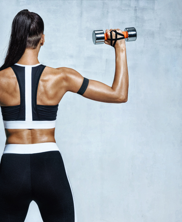 Photo pour Strong woman working out with dumbbells, flexing her arm. Photo of sporty woman in sportswear on grey background. Rear view - image libre de droit