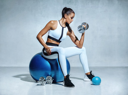 Photo pour Strong woman working out with dumbbells sitting on gymnastic ball. Photo of sporty latin woman in sportswear on grey background. Sports - image libre de droit