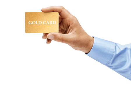 Foto de Man's hand in shirt holding gold credit card isolated on white background. High resolution product. Close up. - Imagen libre de derechos