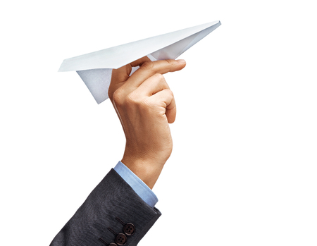 Foto de Man's hand in suit holding paper plane isolated on white background. Close up. High resolution product - Imagen libre de derechos