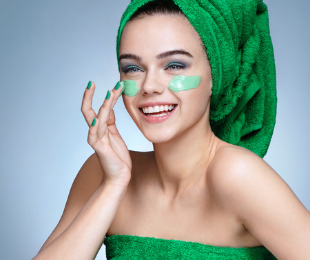 Photo pour Laughing girl applying moisturizing cream on her face. Photo of young girl with flawless skin in green towels. Skin care and beauty concept - image libre de droit