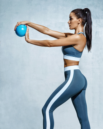 Photo pour Sporty girl with ball for gymnastics. Photo of strong young girl in training muscles hands on grey background. Strength and motivation - image libre de droit