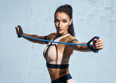 Foto de Athletic girl performs exercises using a resistance band. Photo of young girl on drey background. Strength and motivation - Imagen libre de derechos