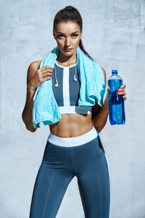 Foto de Attractive woman with muscular body holding bottle of refreshing water. Resting time. Health concept - Imagen libre de derechos