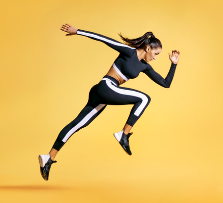 Foto de Sporty woman runner in silhouette on yellow background. Photo of attractive woman in fashionable sportswear. Dynamic movement. Side view. Sport and healthy lifestyle - Imagen libre de derechos