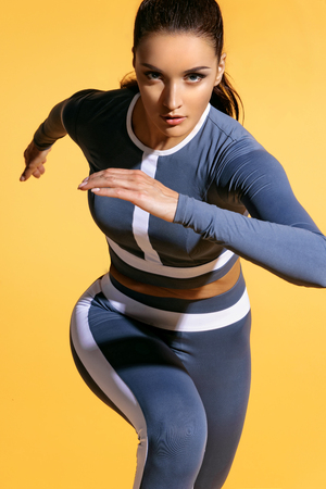 Photo pour Attractive woman runner in fashionable sportswear on yellow background. Dynamic movement. Close up. Sport and healthy lifestyle - image libre de droit