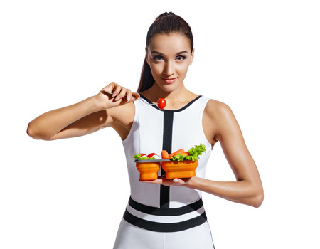 Photo pour Sporty girl holding container with healthy nutrition. Photo of fitness model in fashionable sportswear isolated on white background. Healthy nutrition - image libre de droit