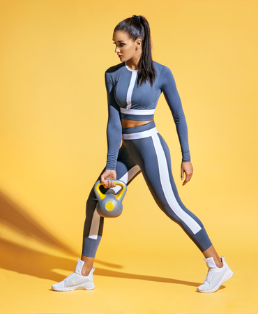 Foto de Sporty woman training muscles of hands and legs using a kettlebell. Photo of latin woman in fashionable sportswear on yellow background. Strength and motivation. - Imagen libre de derechos