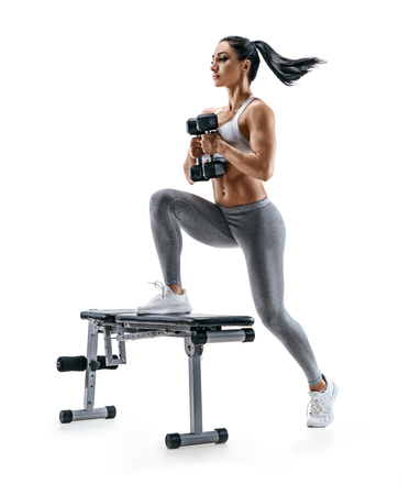 Photo pour Fitness woman doing jump step ups exercise with dumbbells on bench. Photo of attractive woman in sportswear isolated on white background. Strength and motivation - image libre de droit