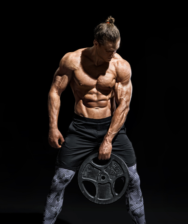 Photo for Sportive young man resting after workout with heavy weight disks. Photo of athletic man with naked torso and good physique on black background. Strength and motivation - Royalty Free Image