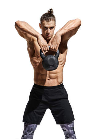 Photo pour Young muscular man training with kettlebell. Photo of athletic man with naked torso and perfect physique on white background. Strength and motivation - image libre de droit