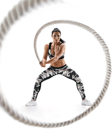 Foto de Woman doing exercises with battle rope. Photo of muscular model in military sportswear isolated on white background. Strength and motivation - Imagen libre de derechos