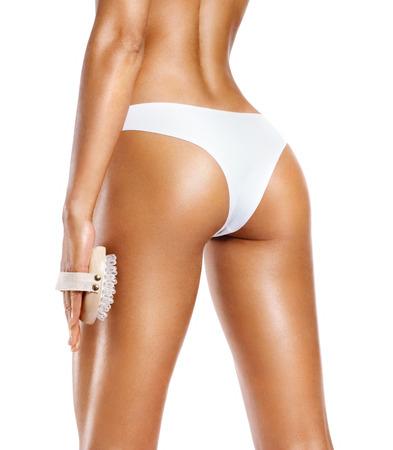 Foto de Woman using anti-cellulite massager. Photo of tanned slim body isolated on white background. Body care concept - Imagen libre de derechos