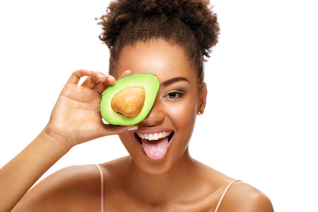 Photo for Funny girl holding half an avocado in front of her face and showing tongue. Photo of smiling african american woman on white background. Beauty & Skin care concept - Royalty Free Image