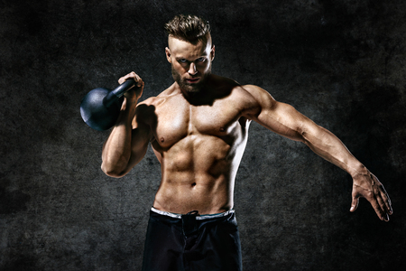Photo for Sporty man working out with a kettlebell. Photo of man on dark background. Strength and motivation - Royalty Free Image