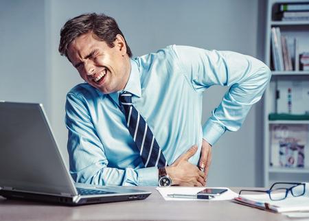 Foto de Employee suffers from severe pain in back. Photo of man working in the office. Medical concept. - Imagen libre de derechos