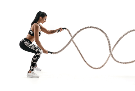 Foto de Strong muscular woman working out with battle ropes. Photo of attractive woman in fashionable sportswear isolated on white background. Strength and motivation. Side view. - Imagen libre de derechos
