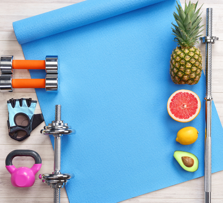Foto de Sports equipment and healthy food on a white wooden background. Top view. Motivation - Imagen libre de derechos