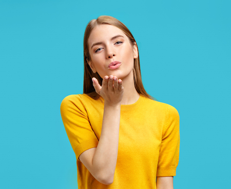Photo pour Cute girl blows kiss at camera, demonstrates love or says goodbye on distance. Photo of girl in yellow sweater on blue background - image libre de droit