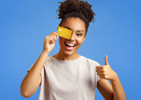 Photo pour Happy girl holds credit card and shows thumb up. Photo of african american girl wears casual outfit on blue background. Emotions and pleasant feelings concept. - image libre de droit