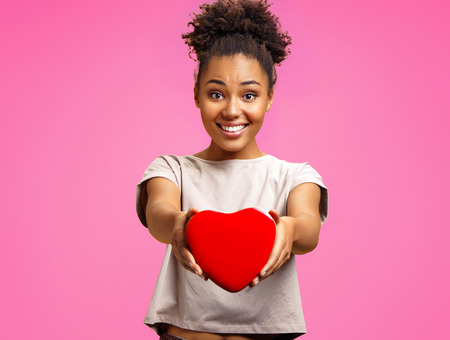 Photo pour Lovely young girl holds heart shaped gift box. Photo of african american girl wears casual outfit on pink background. Emotions and pleasant feelings concept. - image libre de droit