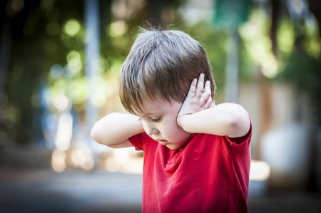 Foto de A 4 year old autistic child in a red shirt closing his ears with hands as if protecting from noise. Autism concept, asperger syndrome, loud noise, scared little kid, parents divorce trauma - Imagen libre de derechos