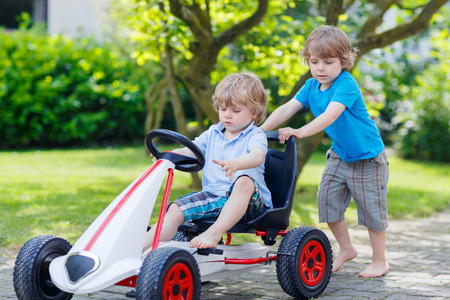 Two happy active little kid and sibling boys having fun with toy race car in summer garden, outdoors. Adorable brother pushing the car with younger child. Outdoor games for children in summer concept.