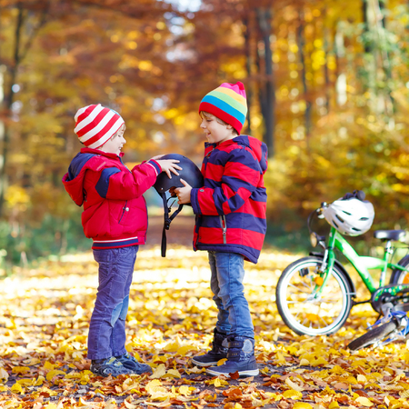 Two little kids boys, best friends in autumn forest. Older brother helping younger child to put his bike helmet. Active siblings with bicycles.
