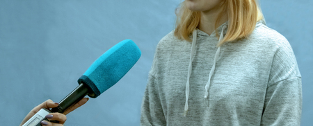 Photo for The girl the blonde in a sports light sweater gives interviews. Abstract image of a teenager. Female correspondent hand is holding a blue microphone. Copy space. The concept of news reporting. - Royalty Free Image