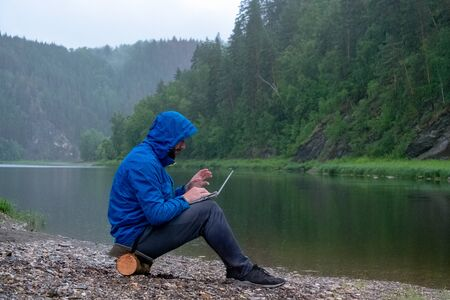 Photo pour The guy in the blue jacket with a hood work on the laptop in and sits on the bank of the river in the rain. Bad weather on the moauntains. Traveler, geologist or tourist with waterproof IT equipment. - image libre de droit