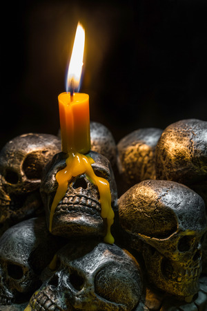 Photo pour skulls with candle burning on wooden background in the darkness - image libre de droit