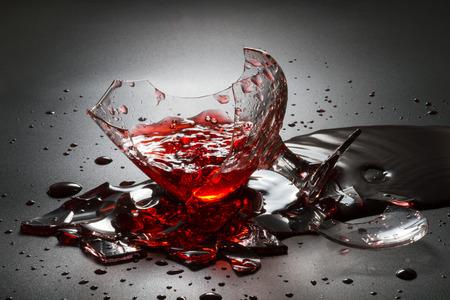 Foto de Pouring red wine on broken glass. - Imagen libre de derechos