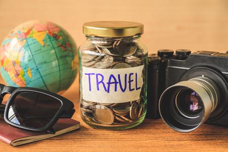 Foto de Coins in glass jar with accessories of traveler on wooden table. Saving money for travel concept - Imagen libre de derechos