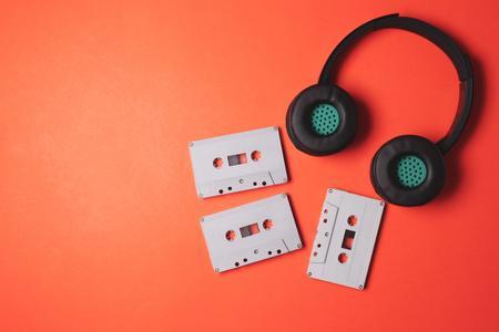 Foto de Modern headphones with Audio cassette tapes on a orange background. Free space for text - Imagen libre de derechos