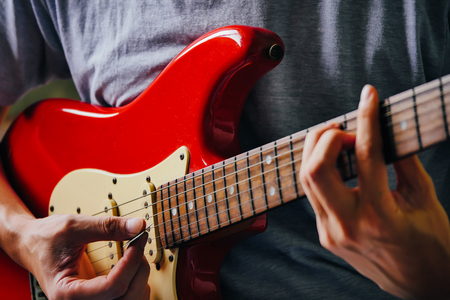 Photo pour Close up of male hands playing electric guitar. Selective focus - image libre de droit
