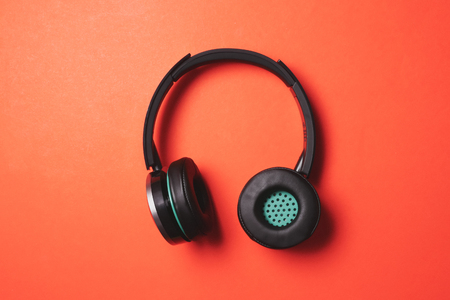 Photo pour Modern headphones on a orange background. - image libre de droit