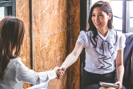 Foto de Successful business people shaking hands, finishing up a meeting. - Imagen libre de derechos