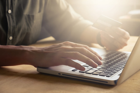 Foto de technology, shopping and banking concept - Close up of casual man holding credit card and using laptop on the table, toned with sunlight - Imagen libre de derechos