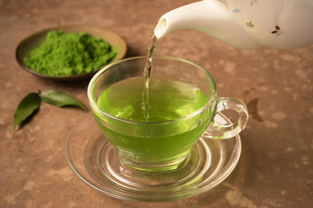 Photo for Green tea being poured into glass tea cup on the table - Royalty Free Image