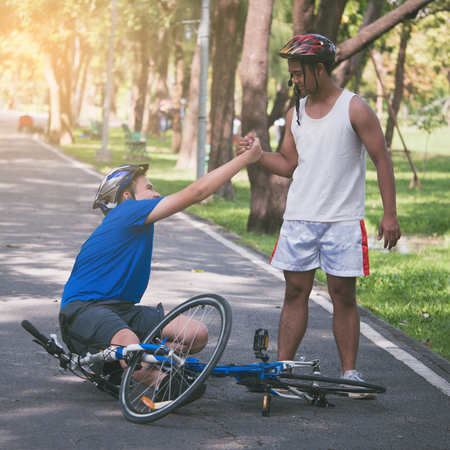 Foto de A young man helps his friend who get bicycle accident on a path. - Imagen libre de derechos