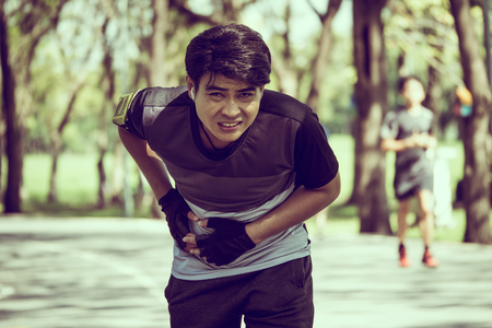 Foto für An Asian man has a stomachache while exercising in a park. - Lizenzfreies Bild